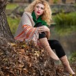 Beautiful woman posing in park during autumn season. Blonde girl wearing green blouse and big shawl posing outdoor. Long fair hair girl with green sweater under a shawl relaxing in autumnal park. — Stock Photo #35111445