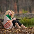 Beautiful woman posing in park during autumn season. Blonde girl wearing green blouse and big shawl posing outdoor. Long fair hair girl with green sweater under a shawl relaxing in autumnal park. — Foto de Stock   #35111451