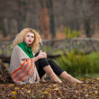 Beautiful woman posing in park during autumn season. Blonde girl wearing green blouse and big shawl posing outdoor. Long fair hair girl with green sweater under a shawl relaxing in autumnal park. — Стоковое фото #35111451