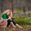 Beautiful woman posing in park during autumn season. Blonde girl wearing green blouse and big shawl posing outdoor. Long fair hair girl with green sweater under a shawl relaxing in autumnal park. — Foto de Stock   #35111461