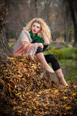 Beautiful woman posing in park during autumn season. Blonde girl wearing green blouse and big shawl posing outdoor. Long fair hair girl with green sweater under a shawl relaxing in autumnal park. — Stock Photo