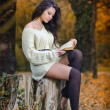 Young Caucasian sensual woman reading a book in a romantic autumn scenery. Portrait of pretty young girl in the forest in autumn day. Fashion portrait of a beautiful young woman in autumn forest — Stock Photo