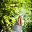 Lovely young lady wearing elegant white dress enjoying the beams of celestial light on her face in enchanted woods. Pretty blonde fairy lady with white dress. Glamorous princess in the woods — Stock Photo