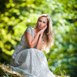 Stock Photo: Lovely young lady wearing elegant white dress enjoying beams of celestial light on her face in enchanted woods. Pretty blonde fairy lady with white dress. Glamorous princess in woods