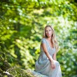 Lovely young lady wearing elegant white dress enjoying the beams of celestial light on her face in enchanted woods. Pretty blonde fairy lady with white dress. Glamorous princess in the woods — Stock Photo #35445831