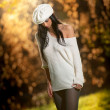 Beautiful sexy girl in white posing in park in autumn day. Beautiful elegant woman with white cap in autumn park. Young pretty brunette woman with leggings and long legs in the forest — Stok fotoğraf
