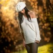 Beautiful sexy girl in white posing in park in autumn day. Beautiful elegant woman with white cap in autumn park. Young pretty brunette woman with leggings and long legs in the forest — Stock fotografie