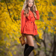 Beautiful elegant woman with orange coat posing in park in autumn. Young pretty woman with blonde hair spending time in autumnal park. Long legs sensual blonde with black leggings waking in forest — Stock Photo #35588867