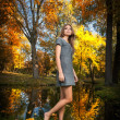 Beautiful elegant woman with short dress posing in park in autumn. Young pretty woman with blonde hair spending time in autumnal park. Long legs sensual blonde with walking in forest — Стоковая фотография