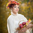 Beautiful creative makeup and hair style in outdoor shoot. Beauty Fashion Model Girl with Autumnal Make up and Hair. Fall. Beautiful fashionable girl with leaves in hair holding a basket with apples. — Stock Photo