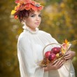 Beautiful creative makeup and hair style in outdoor shoot. Beauty Fashion Model Girl with Autumnal Make up and Hair. Fall. Beautiful fashionable girl with leaves in hair holding a basket with apples. — Stock Photo #36026961