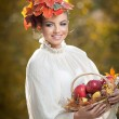 Beautiful creative makeup and hair style in outdoor shoot. Beauty Fashion Model Girl with Autumnal Make up and Hair. Fall. Beautiful fashionable girl with leaves in hair holding a basket with apples. — Foto Stock