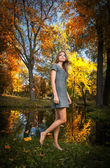 Beautiful elegant woman with short dress posing in park in autumn. Young pretty woman with blonde hair spending time in autumnal park. Long legs sensual blonde with walking in forest — Stock Photo