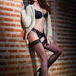 Beautiful brunette womin black sensual lingerie posing provocatively in front of brick wall. Young model wearing black stockings posing pretty. Caucasimodel standing near red brick wall — Stok Fotoğraf #36213747
