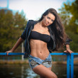 Sexy brunette in denim shorts posing provocatively outdoor. Portrait of a beautiful sexy woman with denim shorts in a park. Attractive female brunette woman posing in blue jeans shorts near a river. — Stock Photo
