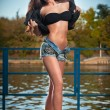 Sexy brunette in denim shorts posing provocatively outdoor. Portrait of a beautiful sexy woman with denim shorts in a park. Attractive female brunette woman posing in blue jeans shorts near a river. — Stock Photo #36365733