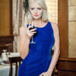 Young beautiful luxurious woman in long elegant dress. Beautiful young blonde woman in blue dress holding a glass of wine. Seductive blonde woman in luxury manor, vintage style — Stock Photo #36461337