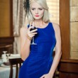 Young beautiful luxurious woman in long elegant dress. Beautiful young blonde woman in blue dress holding a glass of wine. Seductive blonde woman in luxury manor, vintage style — Stock Photo