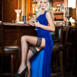 Attractive blonde woman in elegant blue long dress sitting on bar stool holding a glass in her hand. Gorgeous blonde model showing her long legs in black stockings drinking and posing in vintage bar — Stock Photo