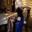 Attractive blonde woman in elegant long dress sitting near a table in a luxurious classic interior. Gorgeous blonde model showing her long legs in black stockings. Sensual lady in a vintage scenery — Stok fotoğraf