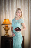 Young beautiful luxurious woman in long elegant dress. Beautiful young blonde woman in turquoise dress with curtains in background. Seductive blonde woman in lace dress in luxury manor, vintage style — Stock Photo
