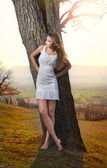 Pretty young woman posing near a tree. Very attractive blonde girl with white short dress outdoor on a hill. Romantic young woman posing outdoor in the field — Stock Photo