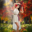 Portrait of beautiful lady in the forest. Girl with fairy look in autumnal shoot. Girl with Autumnal Make up and Hair style. Romantic women with short white dress and red flower in her hair — Stock Photo #36879255