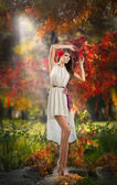 Portrait of beautiful lady in the forest. Girl with fairy look in autumnal shoot. Girl with Autumnal Make up and Hair style. Romantic women with short white dress and red flower in her hair — Stock Photo