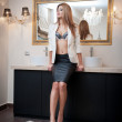 Sensual elegant woman in office outfit staying in front of a large mirror. Beautiful and sexy blonde young woman wearing sexy bra under an elegant jacket posing near a mirror. Fashionable model. — Stock Photo #37073999