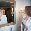 Sensual elegant woman in office outfit looking into a large mirror. Beautiful and sexy blonde young woman wearing an elegant white jacket posing in a mirror. Fashionable model. — Stock Photo #37074007