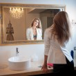 Sensual elegant woman in office outfit looking into a large mirror. Beautiful and sexy blonde young woman wearing an elegant white jacket posing in a mirror. Fashionable model. — Stock Photo #37074009
