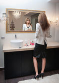 Sensual elegant woman in office outfit looking into a large mirror. Beautiful and sexy blonde young woman wearing an elegant white jacket and a black midi skirt posing in a mirror. Fashionable model. — Stock Photo