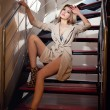 Full-length portrait of blonde woman wearing a coat posing provocatively on steps in a modern interior. Beautiful woman in casual style coat and high heel shoes on stairs full body shoot indoor — Stock Photo #37141257