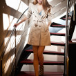 Full-length portrait of blonde woman wearing a coat. Beautiful young woman in coat descending steps in modern interior. Woman in casual style coat and high heel shoes on stairs full body shoot indoor — Stock Photo #37141263