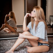 Young blond sensual woman sitting on the floor thinking. Beautiful young girl with comfortable clothes relaxing on the carpet  with a mirror in background. Attractive blonde in cosy scenery, indoor. — Stock Photo