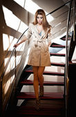 Full-length portrait of blonde woman wearing a coat. Beautiful young woman in coat descending steps in modern interior. Woman in casual style coat and high heel shoes on stairs full body shoot indoor — Stock Photo