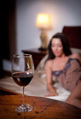 Mysterious lady laying in bed with a glass of red wine foreground. Sensual woman on bed and glass of wine. Beautiful girl in sensual lingerie posing provocatively indoor, relaxation moments — Stock Photo