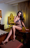 Attractive sexy brunette in lingerie posing challenging. Portrait of sensual woman wearing provocative lingerie in classic boudoir scene. Long hair brunette wearing boudoir outfit in vintage room — Stock Photo