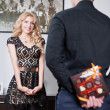 Attractive blonde girl smiling and waiting a surprise from her boyfriend. Man hiding behind a candies box of girlfriend. Man holding a box of chocolate at his back to make a gift to his girlfriend. — Stock Photo