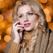 Portrait of young beautiful woman with long fair hair outdoor in a cold winter day. Beautiful blonde girl in winter clothes with xmas lights in background. Beautiful woman dreaming in winter scenery — Stock Photo #37611015