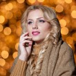 Portrait of young beautiful woman with long fair hair outdoor in a cold winter day. Beautiful blonde girl in winter clothes with xmas lights in background. Beautiful woman dreaming in winter scenery — Stock Photo #37611019