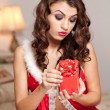 Stock Photo: Young sexy Santa holding a gift, boudoir shoot. Attractive brunette with long hair wearing a provocative lingerie Xmas style receiving a red little box as Xmas present. Beautiful young woman in red