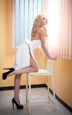 Young blonde woman wrapped in white towel looking on the window. Beautiful young woman with a towel around her body after bath on high heels. Side view of long fair hair girl with her knee on a chair. — Stock Photo