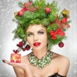 Beautiful creative Xmas makeup and hair style indoor shoot. Beauty Fashion Model Girl. Winter. Beautiful attractive girl with Christmas tree accessories in studio holding a gift. — Stock Photo #37712987