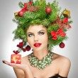 Beautiful creative Xmas makeup and hair style indoor shoot. Beauty Fashion Model Girl. Winter. Beautiful attractive girl with Christmas tree accessories in studio holding a gift. — Stock Photo #37712989