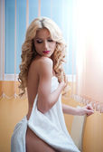 Young blonde woman wrapped in white towel posing relaxed. Beautiful young woman with a towel around her body after bath. Side view of long fair hair girl sitting on chair exposing her shoulder. — Stock Photo