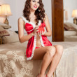 Young sexy Santa holding a gift, boudoir shoot. Attractive brunette with long hair wearing a provocative lingerie Xmas style receiving a red little box as Xmas present. Beautiful young woman in red — Stock Photo
