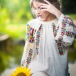 Young girl wearing Romanitraditional blouse holding sunflower outdoor shot. Portrait of beautiful blonde girl with bright yellow flower. Beautiful womlooking at flower harmony concept — Stock Photo #37812861