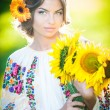 Young girl wearing Romanian traditional blouse holding sunflowers outdoor shot. Portrait of beautiful blonde girl with bright yellow flowers bouquet. Beautiful woman with yellow flower in hair posing — Stock Photo #37812873