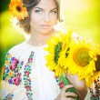 Young girl wearing Romanian traditional blouse holding sunflowers outdoor shot. Portrait of beautiful blonde girl with bright yellow flowers bouquet. Beautiful woman with yellow flower in hair posing — Stock Photo #37812879